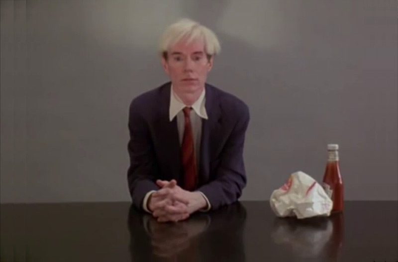 Still from Andy Warhol eating a Hamburger from the film 66 Scenes from America (1982) by Jørgen Leth. Courtesy the artist and Louisiana Museum of Modern Art.